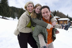 Portrait of young family with daughter in snow royalty free stock photo