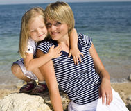 Portrait of young family having fun on the beach, mother and daughter at sea Stock Photo