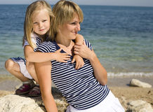 Portrait of young family having fun on the beach, mother and daughter at sea Royalty Free Stock Photography
