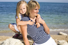 Portrait of young family having fun on the beach, mother and daughter at sea Royalty Free Stock Images