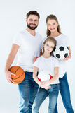Portrait of young family holding different sports balls. On white stock photos
