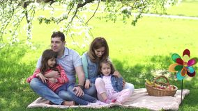 Portrait of a young family. parents spend time with their children outdoors. a picnic under a blossoming Apple tree. stock video