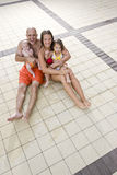Portrait of young family on pool deck tile Stock Image