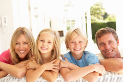 Portrait Of Young Family Relaxing Together On Sofa Royalty Free Stock Photos