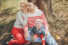 Portrait young family resting under a tree Stock Photo