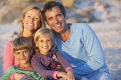 Portrait Of Young Family Sitting On Beach Stock Image