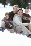 Portrait of young family sitting in snow Stock Photo