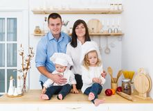 Portrait of a young family with small children in white caps in the kitchen at home royalty free stock images