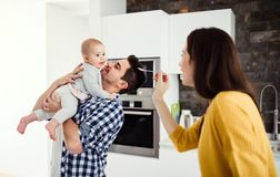 A young family at home, a man holding a baby and a woman feeding her. A portrait of young family standing in a kitchen at home, a men holding a baby and a women stock photography