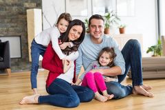 Portrait of a young family with two children at home. Royalty Free Stock Photos