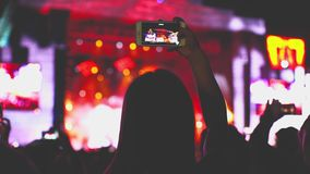 Portrait of young fan girl on open air rock techno pop fest staying under stage scene and shoot concert on her. Smartphone technology stock video footage