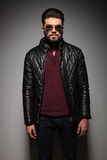 Portrait of a young fashion man with long beard. Wearing a leather jacket and sunglasses Royalty Free Stock Photography