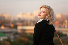 Young blond fashion woman in black coat outdoor Royalty Free Stock Photography