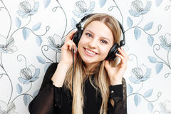 Portrait of young fashionable blonde woman enjoying music in big dj headphones indoors Stock Photo