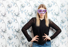 Portrait of young fashionable blonde woman posing in mask against a wall with vintage wallpapers pattern Stock Images