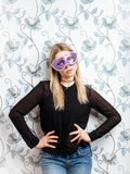 Portrait of young fashionable blonde woman posing in mask against a wall with vintage wallpapers pattern Stock Photo