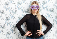 Portrait of young fashionable blonde woman posing in mask against a wall with vintage wallpapers pattern. Young fashionable blonde woman posing in mask against a Royalty Free Stock Photos