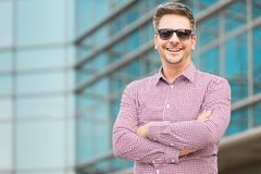 Successful entrepreneur standing in front of modern business building. stock photo