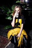 Portrait of a young fashionable girl in black urban outfit and yellow jacket sitting in modern cafe and drinking coffee stock photos