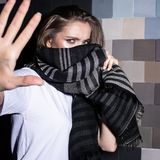 Portrait of a young fashionable girl in a white T-shirt covers her face with a striped scarf makes a prohibitive gesture royalty free stock photos