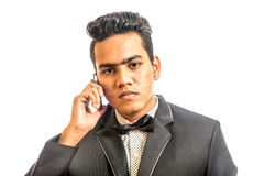 Portrait of young fashionable man. Studio portrait of young man with glasses wearing suite and necktie. He is talking over mobile phone Stock Photo