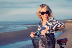 Portrait of young fashionable woman with bicycle on the beach Stock Images