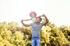 Portrait of young father carrying his daughter on his back royalty free stock photography
