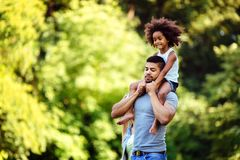 Portrait of young father carrying his daughter on his back Stock Images
