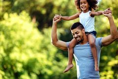 Portrait of young father carrying his daughter on his back Royalty Free Stock Image