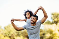 Portrait of young father carrying his daughter on his back Royalty Free Stock Photo