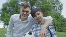 Portrait of a young father hugging his son. Joyful smiling boy holding a soccer ball. Family leisure outdoors. Father. Portrait young father hugging his son stock video footage