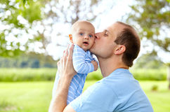 Portrait of young father kissing his newborn son. Portrait of young Caucasian father holding his newborn son and kissing him. Little boy looking at camera stock images
