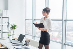 Portrait of a young female assistant planning work day schedule, writing down timetable, standing in office. Stock Image