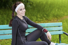 Portrait of Young Female Athlete Relaxing on Bench in the Park. Stock Image
