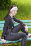 Portrait of Young Female Athlete Relaxing on Bench in the Park. Royalty Free Stock Image