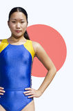 Portrait of young female athlete standing with hands on hips over Japanese flag Stock Images