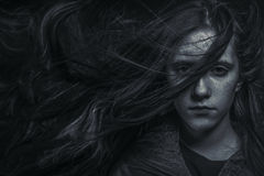 Portrait of young female beauty with long dark hair in black and Stock Photography