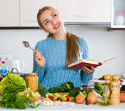 Portrait of young female with book and veggies at home Stock Images