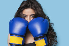 Portrait of a young female boxer with fists up against blue background Royalty Free Stock Image