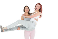 Portrait of a young female carrying her cheerful friend Royalty Free Stock Images