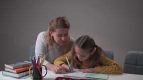 Portrait of young female Caucasian tutor helping her student to do homework. Cute Caucasian girl writing in the exercise stock video footage