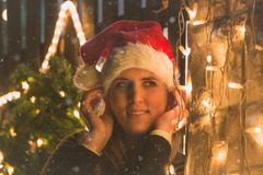 Portrait of young female with Christmas decoration lights outdoors stock image
