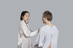 Portrait of a young female doctor examining male patient Royalty Free Stock Photo