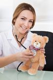 Female Doctor Examining Teddy Bear Stock Photos
