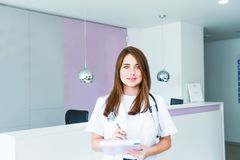 Portrait of young female doctor with note book looking at camera and smiling cheerfully while posing in receptional hall of modern stock photography