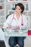 Portrait young female doctor sitting at desk in hospital Royalty Free Stock Image