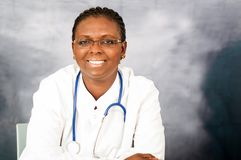 Portrait of a young female doctor. A young female doctor sitting in her office wearing glasses with stethoscope on her neck and smiling at the camera royalty free stock photo