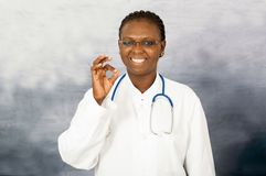 Portrait of young female doctor. Young doctor woman standing in glasses and stethoscope at the neck makes the sign of the hand smiles at the camera royalty free stock image