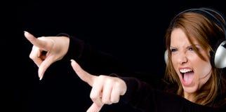 Portrait of young female enjoying music. Portrait of young woman enjoying music and pointing aside Stock Images