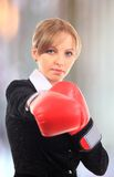 Portrait of  young female entrepreneur wearing boxing gloves aga Stock Image